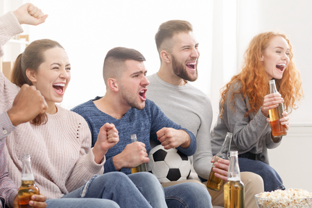 Goal. Happy friends watching match, cheering for favourite team at home