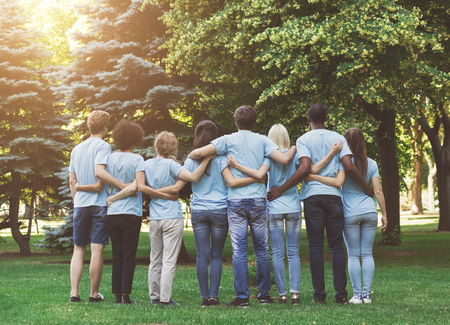 Volunteering and ecology. Group of millennials volunteers embracing in park, back view, empty space Imagens