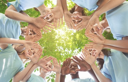 Team of millennial volunteers smiling at camera through palms, standing together in circle, view from below, empty space