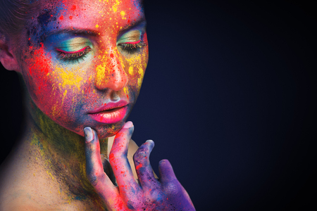 Fashion model portrait with colorful artistic bodypaint, black studio background