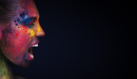 Furious girl with bright artistic bodypaint screaming at empty space, black panorama background