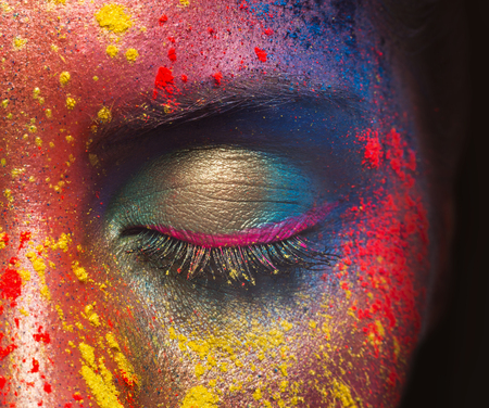 Holi colors festival. Closed eye of female beauty model with bright colorful powder art make-up on black background, closeup Stock Photo