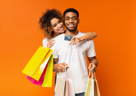 Cheerful african-american couple of shopaholics satisfied with their bank, embracing with credit card and shopping bags on orange background 版權商用圖片