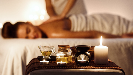 Relaxed woman enjoying aromatherapy massage in luxury spa with candle on foreground