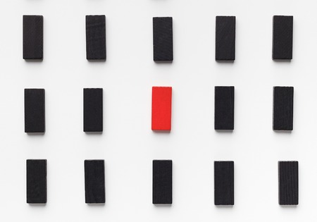 Ageism. Age discrimination shown with one red wooden block between black ones, top view