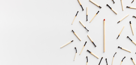 Not like others, individuality and uniqueness concept. One big unused matchstick surrounded by group of burnt ones, panorama, free space
