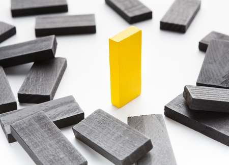 Business competition, championship and survival. One yellow wooden block standing among fallen black ones
