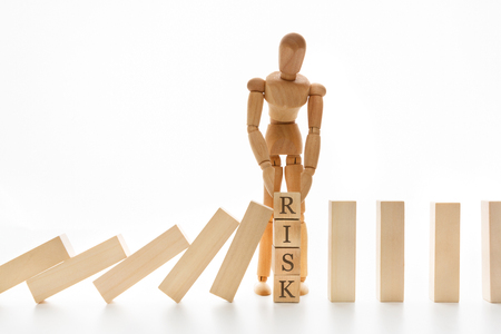 Risk management and insurance concept. Wooden puppet stopping domino effect, leadership has solution for problem