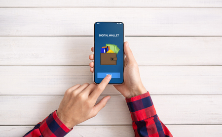 Comercio electrónico. Hombre que usa el teléfono inteligente con la aplicación de billetera digital, vista superior