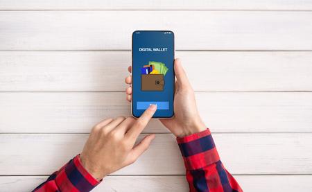 E-commerce. Man met smartphone met digitale portemonnee-applicatie, bovenaanzicht