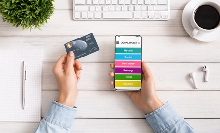 Internet banking. Female hands with mobile phone with digital wallet application and credit card at workplace, paying online, top view Banco de Imagens