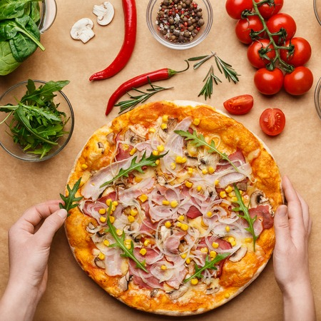 Woman decorating homemade pizza, adding rocket salad, top view, crop