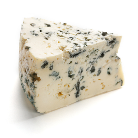 A wedge of full fat soft blue cheese on white background
