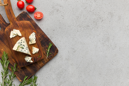 Blue cheese on wooden board, tomatoes and herbs over concrete background, top view, copy space