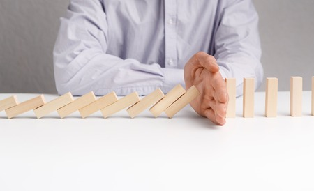 Businessman stopping domino effect on white table. Business success concept, empty space