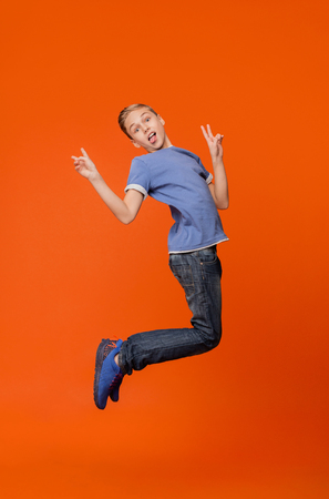 Little ape. Boy grimacing, showing tongue and peace sign, jumping in air on orange studio background Stock Photo