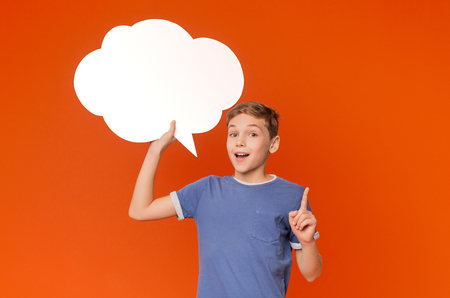 Inspired boy having idea, pointing finger up and holding blank speech bubble, orange studio background Фото со стока