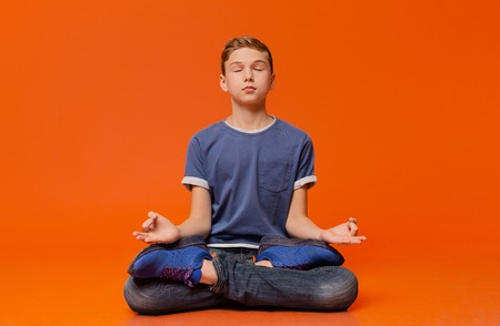 Calm boy sitting on floor and meditating in lotus position, practicing yoga, orange studio background