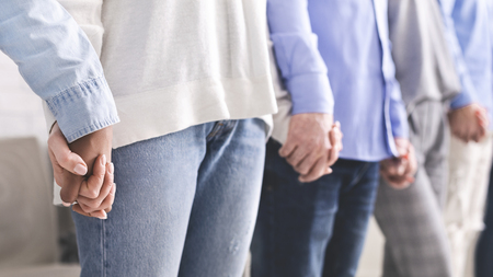 People connection. Young team holding hands of each other during psychological group therapy session, free space