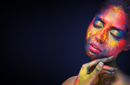 Holi colors festival. Young sensual woman with colorful powder art bodypaint on black studio background, empty space Stock Photo