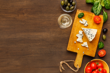 Blue cheese on board, olives and herbs over wooden background, top view, copy space