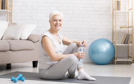 Senior woman resting on exercise mat after fitness workout, having break to drink water, empty space