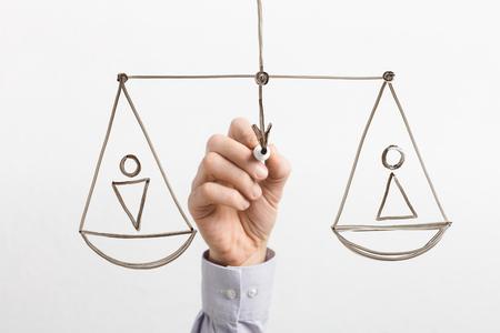 Égalité des genres. Homme dessinant des échelles égales avec des figures masculines et féminines sur verre, fond blanc