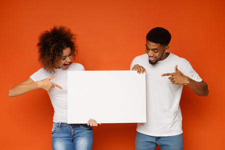 Young happy african-american couple pointing at blank advertising board, orange background, empty space for text