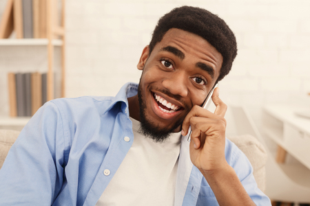 Positive african american guy talking on mobile phone and smiling at camera at home, free space