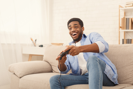 Boys are boys. Excited african american guy playing video game with joystick at home, empty space