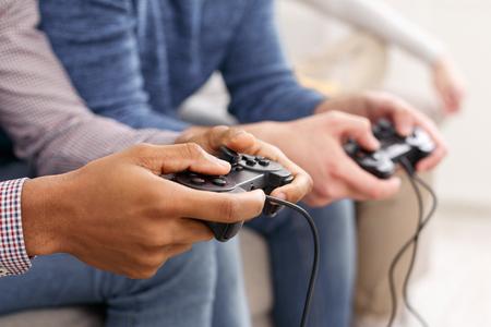 Men playing video games, having fun at home, closeup