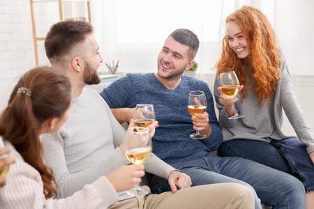 Celebre la reunión. Amigos bebiendo vino y hablando en casa