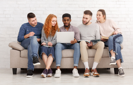 Students preparing for exams together, sitting on sofa over white wall Banco de Imagens