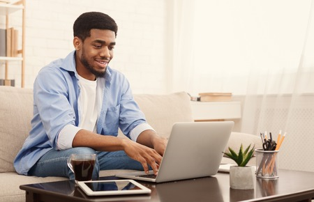 Home office. Positive african american man working on laptop, typing on keyboard, free space