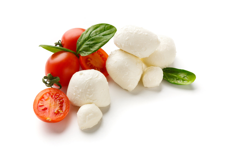 Mozzarella cheese, cherry tomatoes and basil leaves on white background. Caprese salad ingredients concept Imagens
