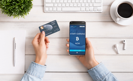 Cryptocurrency and real money. Woman holding credit card and using btc earning application on smartphone, top view