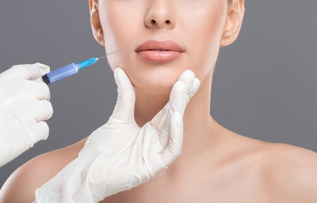 Beauty procedure. Young woman receiving facial skin lifting injections, closeup