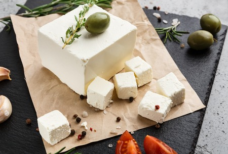 Cubes of feta cheese with olive and rosemary on craft paper over concrete background. Homemade greek cheese concept Reklamní fotografie