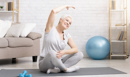 Positive active mature woman warming up, doing stretching exercises at home, free space
