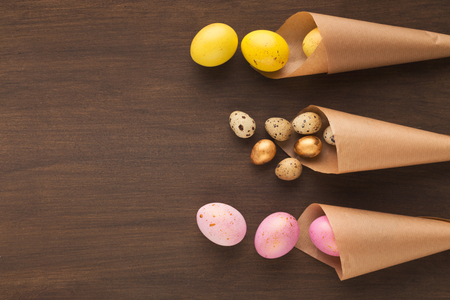 Easter composition with colourful eggs in craft paper cornets, top view, copy space
