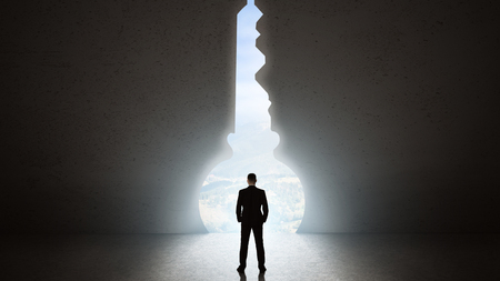 Silhouette of man against giant key shape portal. Free your mind concept