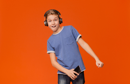 Cute boy in wireless headphones listening to music online on smartphone and dancing, orange background 免版税图像