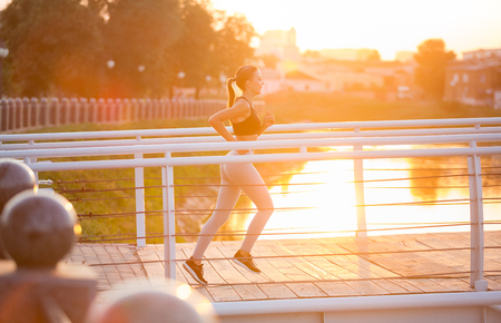 Active lifestyle. Millennial fitness girl jogging on bridge early in morning, sun flare, copy space Standard-Bild