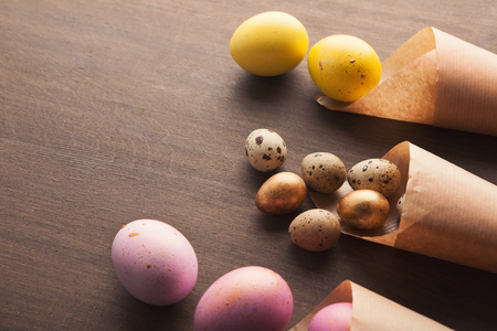Easter composition with colourful eggs in craft paper cornets
