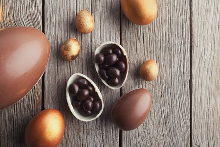 Chocolate easter eggs filled with candies on wooden background, top view Stock Photo