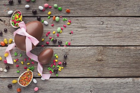 Border of chocolate easter eggs with pink ribbon on wooden background