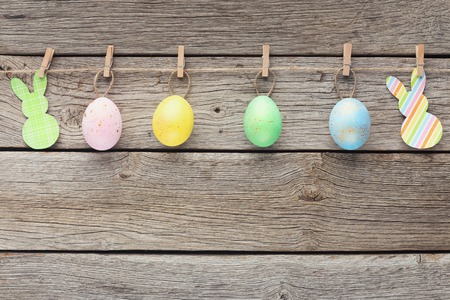 Oeufs de caille colorés et lapins en papier sur corde avec pinces à linge, espace pour copie