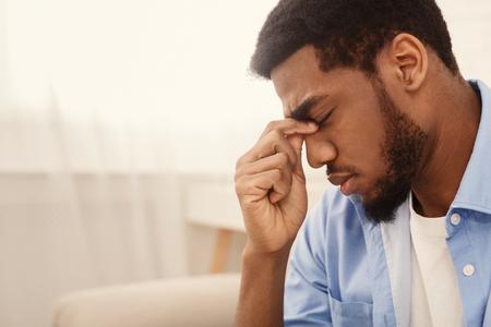 Depressiver Afroamerikaner, der seinen Nasensteg berührt und die Augen geschlossen hält, leerer Raum