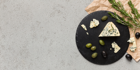 Blue cheese on black board, olives and herbs over concrete background, top view, copy space. Cheese appetizer concept 写真素材 - 120397230