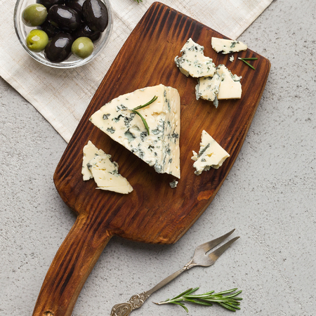 Blue cheese on wooden board with olives and herbs over concrete background, top view 写真素材 - 120397265